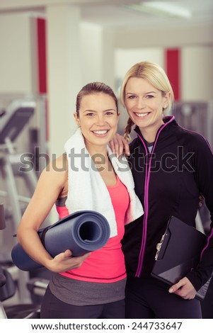 Close up Fit Young Woman with Mat Posing with her Female Gym Instructor at the Fitness Gym.