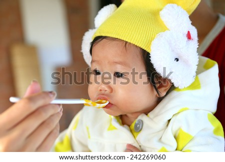 Close up Five month old South East Asian Thai baby girl being spoon fed - stock photo
