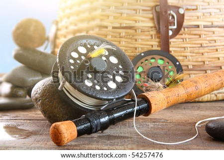 Close-up fly fishing rod and basket against blue sky - stock photo