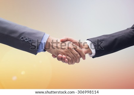 close up focus business man handshake on blurred warm colorful background:adult people in suit outstretched arm hand shaking togetherness for agreement in promise concept:collaboration consult concept - stock photo