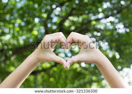 close up focus showing woman hands love symbol on blur green bokeh background at outdoor park:heart shape gesture.happy healthy life:medical healing treat against sickness :safe help living concept - stock photo