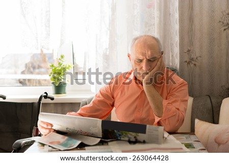 Close up Focused Old Man Sitting at the Living Room While Reading Newspaper with One Hand on his Face. - stock photo