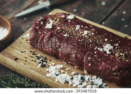 Close up focused piece of meat salted peppered on wooden board on vintage table between spices and herbs ready to grill and cook