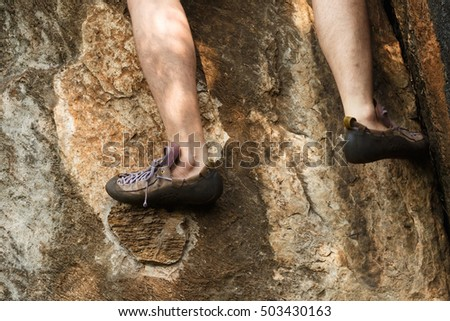 Close up foots and legs climbing up on the rock wall.Rock climbing.Extreme sport.