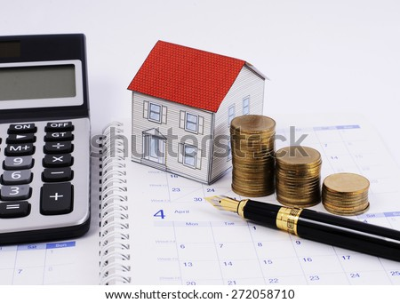 Close up for Fountain pen and money coins stack and paper house and calculator on calendar book pages - stock photo