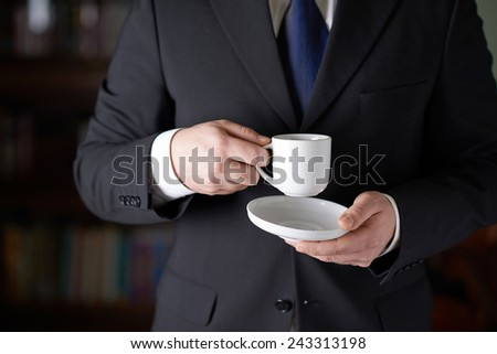 Close-up fragment of a man in a business suit holding a cup of coffee in front of him, shallow depth of field composition - stock photo