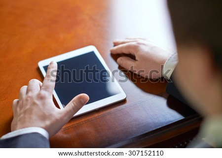 Close-up fragment of a man in a business suit working with the tablet pad device, behind his shoulder close-up composition with a shallow depth of field - stock photo