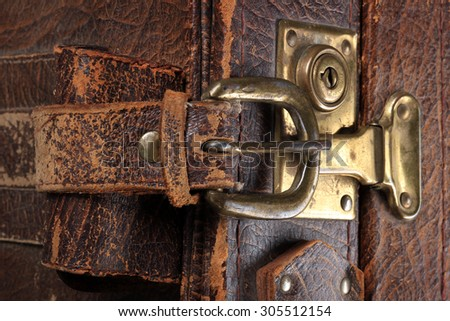 close-up fragment of locks and fasteners on the vintage leather suitcase brown