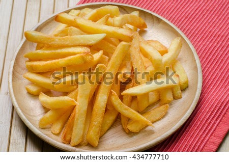 Close up, French fries sprinkled salt on wood plate - stock photo