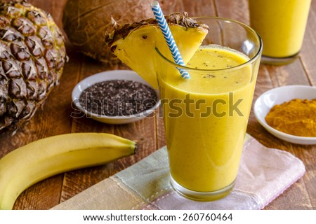 Close up fresh blended fruit smoothies made with pineapple, banana, coconut, turmeric and chia seeds surrounded by raw ingredients in drinking glass with pineapple slice garnish and blue striped straw - stock photo