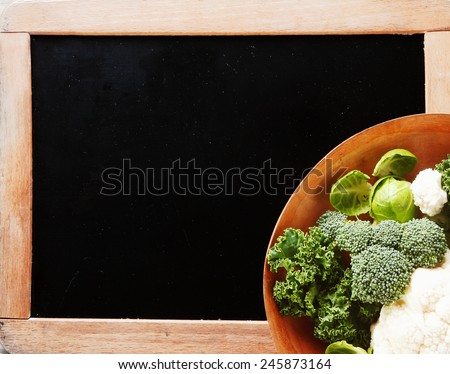 Close up Fresh Broccoli and Cauliflower Veggies, with Brussels Sprout, on Wooden Bowl Placed on Chalkboard Board Corner. Emphasizing Copy Space. - stock photo