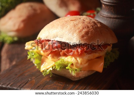Close up Fresh Burger with Egg, Cheese and Bacon, Added with Lettuce, on Top of Wooden Table. - stock photo