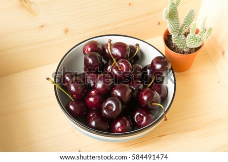 Close up fresh cherries in bowl on table