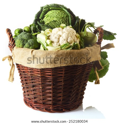 Close up Fresh Farm Vegetables in a Basket, Emphasizing Cauliflower, Brussels Sprouts, Broccoli and Cabbage. Isolated on White Background. - stock photo