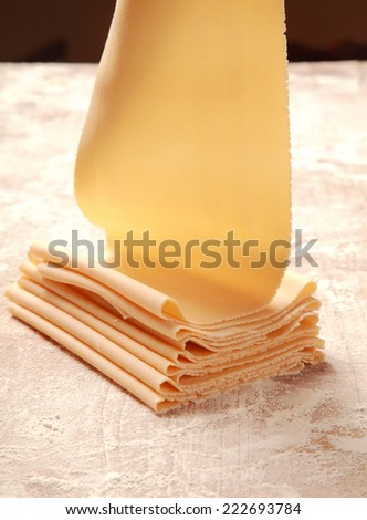 Close up Fresh Italian Egg Flat Pasta Made by Pasta Roller on the Table Filled with Flour. - stock photo