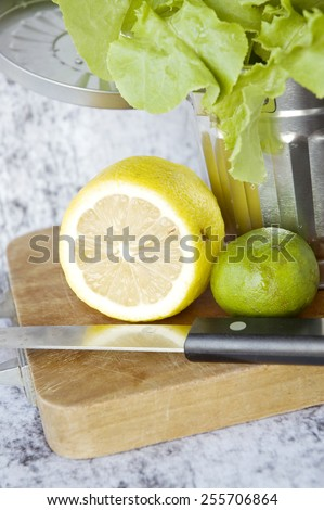close up fresh lemon and lime with lettuce in silver bin - stock photo