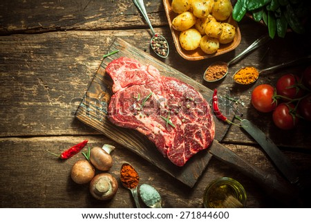 Close up Fresh Pork Meat with Herbs, Spices and Veggies on Top of a Wooden Rustic Table, Captured in High Angle. - stock photo