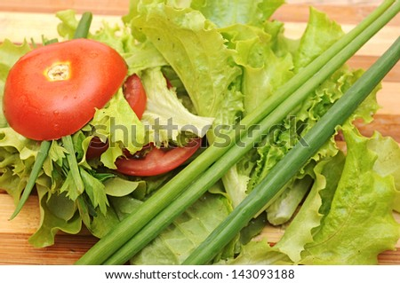 close-up fresh red tomato, green onions, lettuce, parsley, against a wooden board