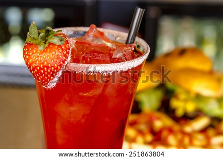 Close up fresh strawberry vodka cocktail with ice and sugar on glass rim garnished with fresh strawberry sitting on bar with napkin and hamburger sliders in background - stock photo