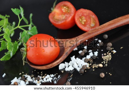 Close up fresh tomato on wooden spoon with sea salt and pepper on background - stock photo
