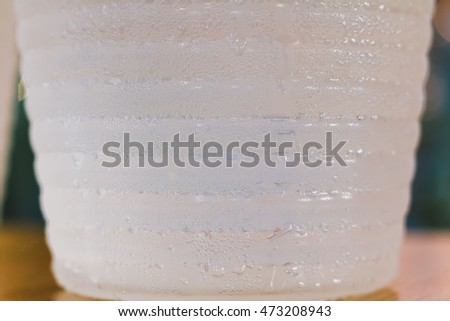 close up Fresh water with ice cubes in glass jug and water drop, select focus