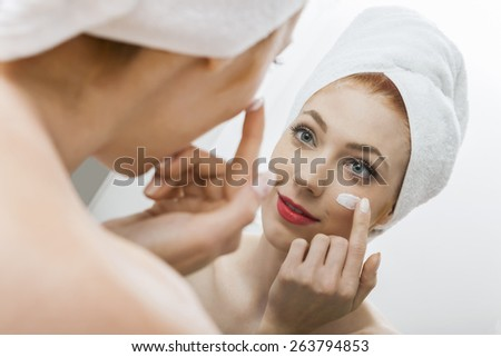 Close up Fresh Woman After Shower Applying White Cream on her Face in Front a Mirror With Towel on her Head.