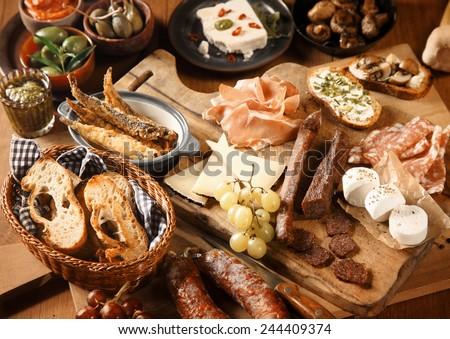 Close up Freshly Made Appetizing Various Tapas on Wooden Table, Emphasizing Bread, Cheese, Grapes and Meats. - stock photo