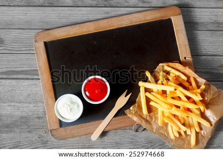 Close up Fried Potatoes Fries and Sauces Above Black Chalkboard with a Wooden Background, Emphasizing Copy Space. - stock photo