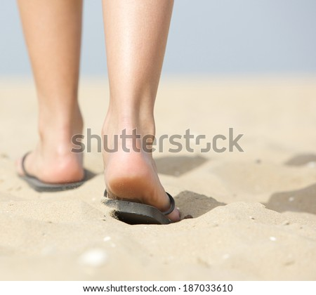 Close up from behind rear view woman walking in slippers on sand at beach - stock photo