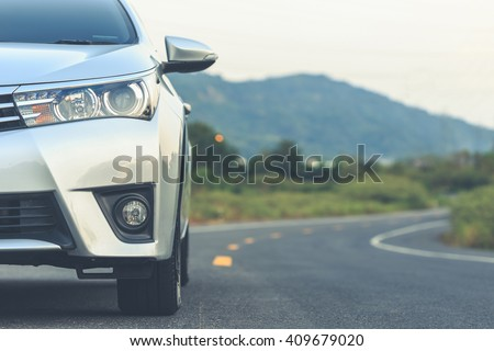 Close up front of new silver car parking on the asphalt road - stock photo