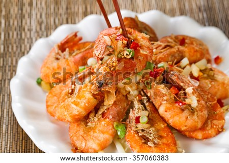 Close up front view of a fried bread coated shrimp, selective focus on single piece in chopsticks, with fresh garnishes.