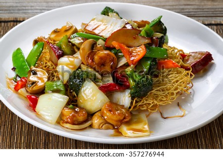 Close up front view of a fried noodle with shrimp, pork, vegetables and sauce in white plate.