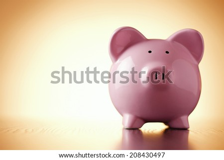 Close-up front view of a funny pink porcelain piggy bank, concept of savings and financial profit