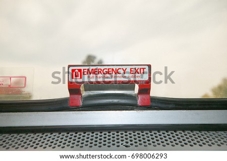Close up front view of a red and white emergency exit sign and latch on the inside of a vehicle window