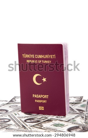 Close up front view of a Turkish passport with Republic of Turkey and Passport text in turkish, on one hundred dollar banknotes, isolated on white background. - stock photo