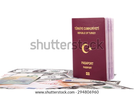 Close up front view of a Turkish passport with Republic of Turkey and Passport text in turkish, on euro and dollar banknotes, isolated on white background. - stock photo
