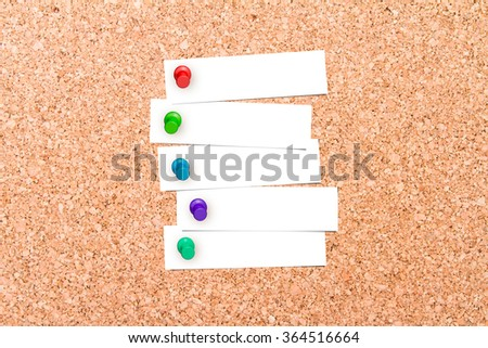Close up front view of illustrative corkboard with blank white note cards pinned with colorful pins, on pinboard background. - stock photo