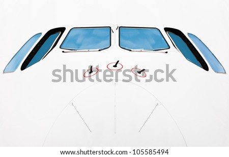 Close up front view of pilot cabin of modern jumbo jet. White plane with blue windows. Lots of copy space. - stock photo