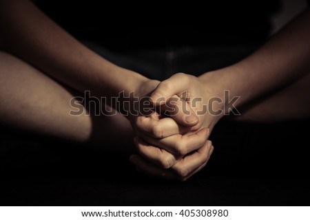 Close up front view on pair of folded hands over crossed legs in sitting position with dark background - stock photo