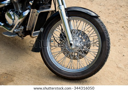Close up front wheel motorcycle chopper  on the floor. - stock photo