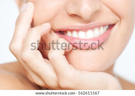 Close up frontal beauty section portrait view of a young woman natural smile with voluptuous pink lips leaning on her hand smiling with white teeth, classic beauty detail indoors.