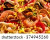 Close up full frame background of delicious seafood paella with prawns and mussels in a bed of saffron rice and vegetables - stock photo