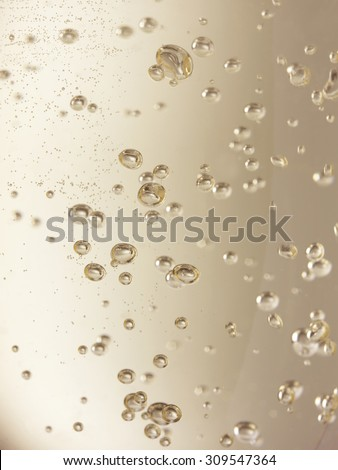 Close up, full frame shot of champagne bubbles in a glass with a shallow depth of field. Please note some bubbles may look like sensor spots as they are more distant and out of focus.  - stock photo