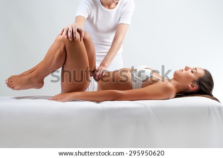 Close up full length portrait of Woman at osteopathic session. Therapist doing manipulative massage on belly.