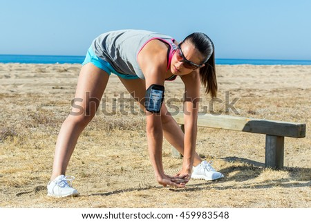 Close up full length portrait of young female runner warming up muscles at beach front.