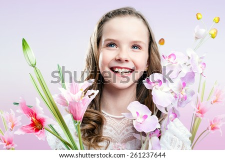 Close up fun portrait of communion girl holding colorful flowers. - stock photo