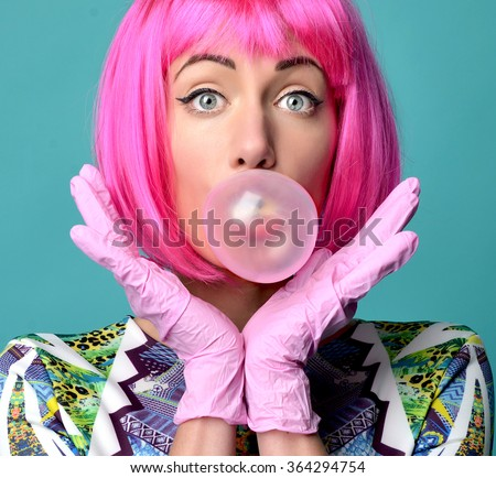 Close up funny fashion portrait of cheerful woman inflating the bubble gum in hot pink party wig on a mint background. - stock photo
