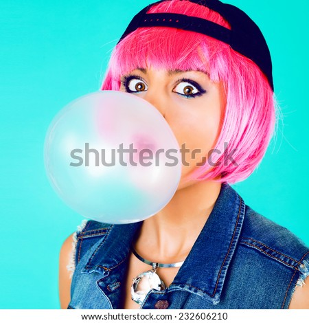 Close up funny fashion portrait of cheerful woman inflating the bubble gum, wearing swag hat, hot pink party wig, denim vest and stylish trendy diamond necklace. Bright sweet colors, mint background. - stock photo