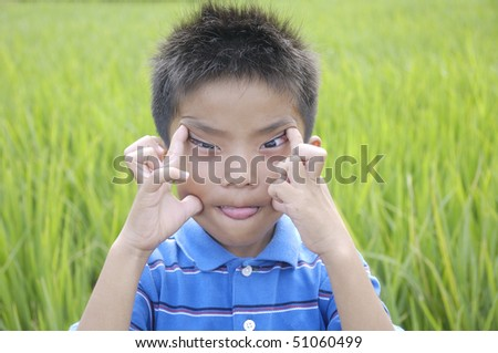 Close up Funny little boy against green rice fields - stock photo