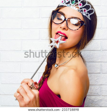 Close up funny portrait of brunette hipster woman, ready for masquerade party wearing sexy fairy costume, stockings, vintage glasses, funny fake crown and liking magic wand . - stock photo